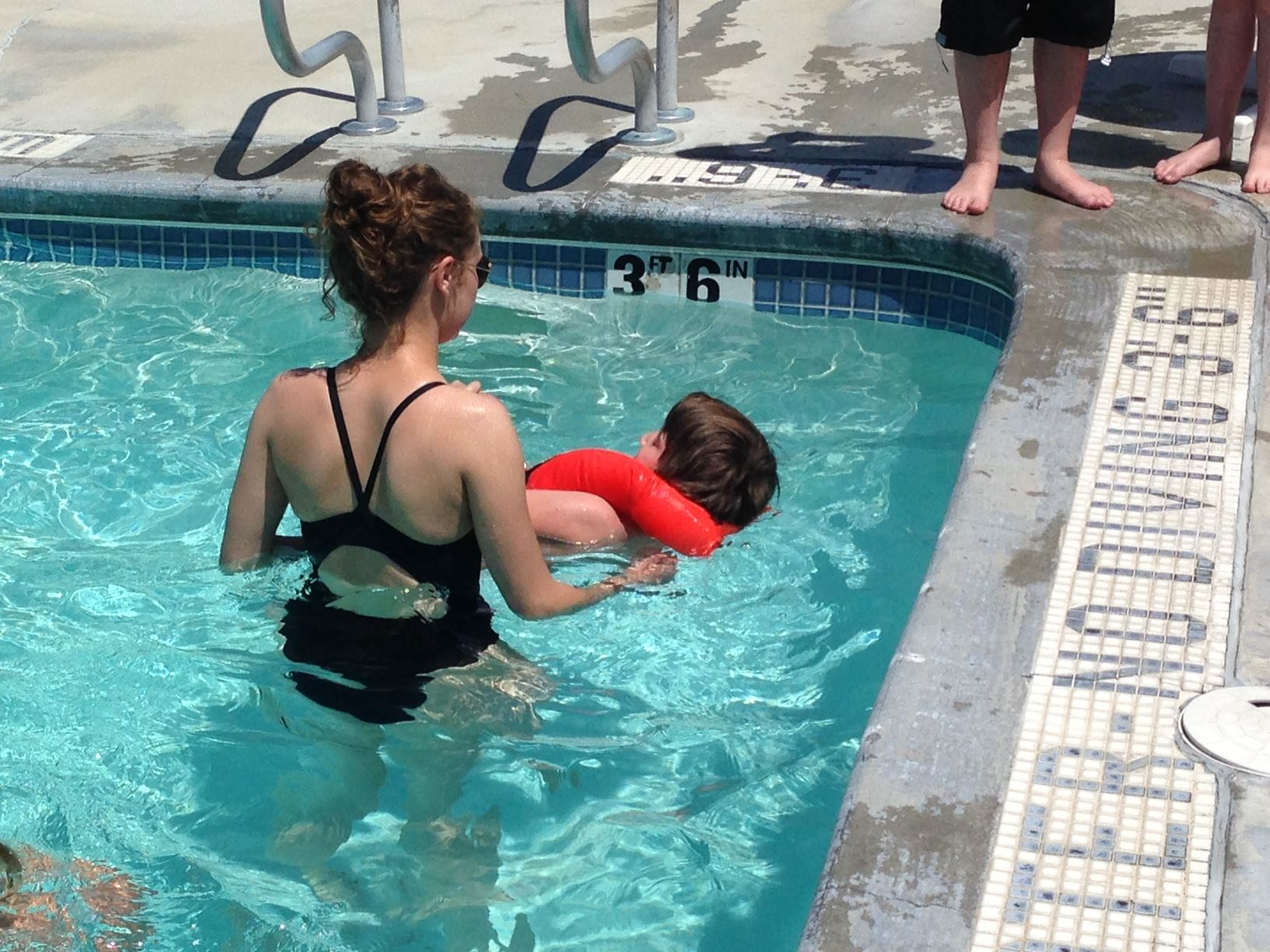 Child floating in swimming pool with lifeguard at Summer Splashtacular