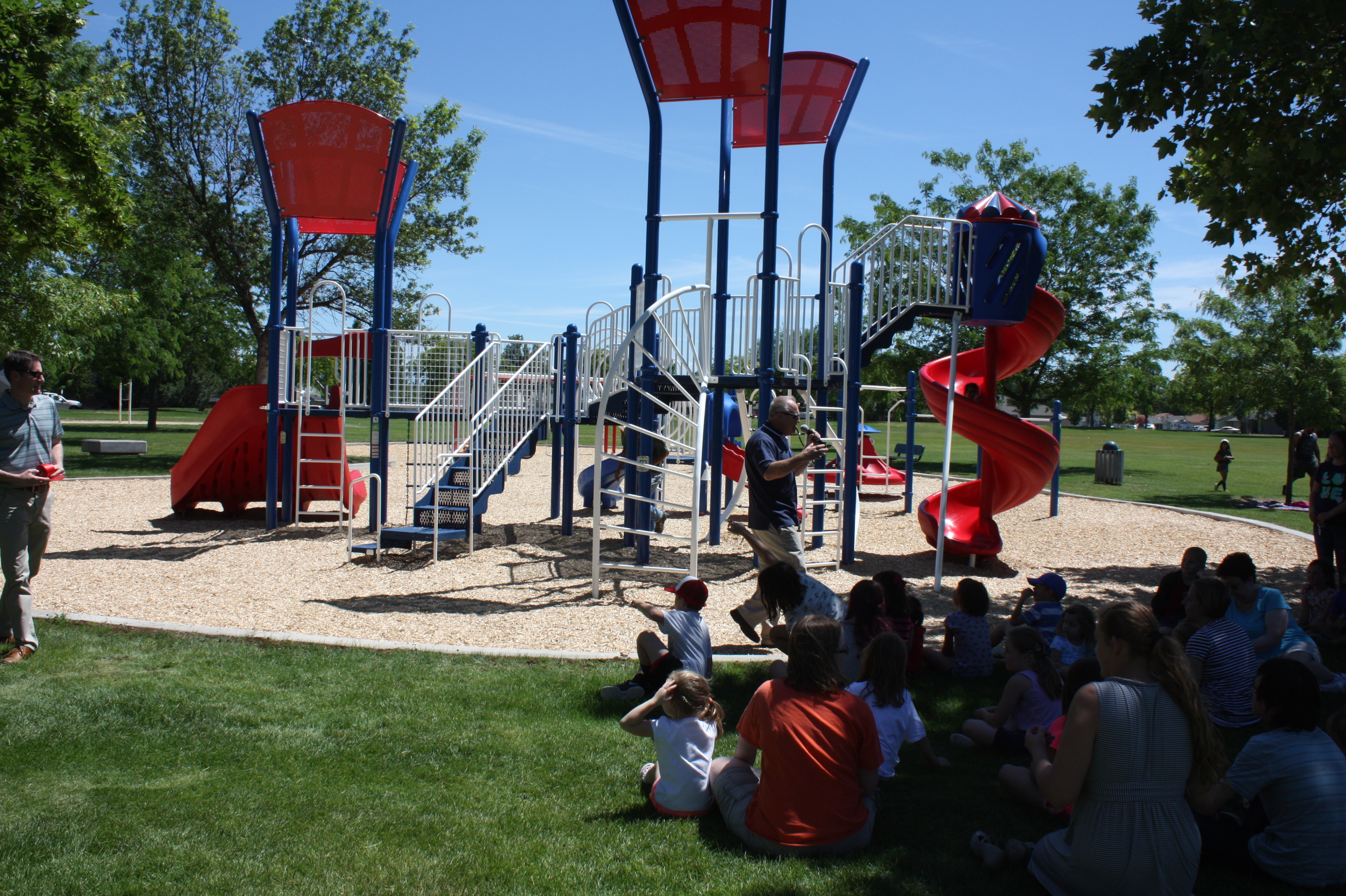 Group of children sitting in front of the play structure at Liberty Park.