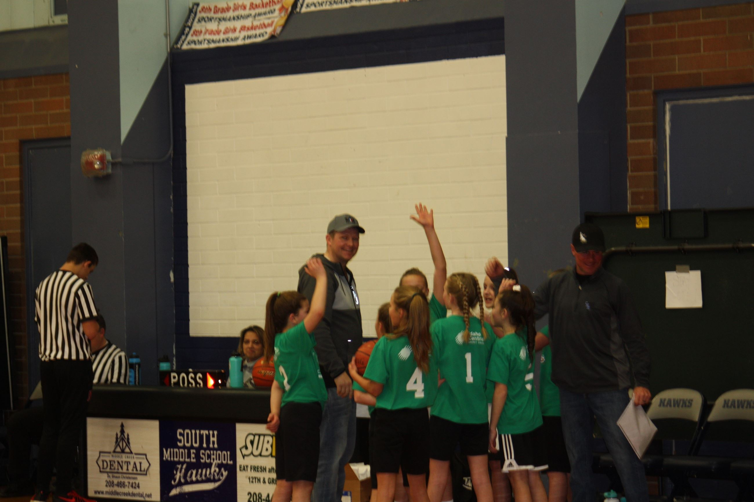 Team of girls in green shirts in a huddle with two adults