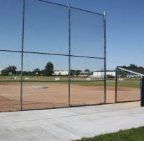 Batting Cage and Dugout Beside a Ball Diamond
