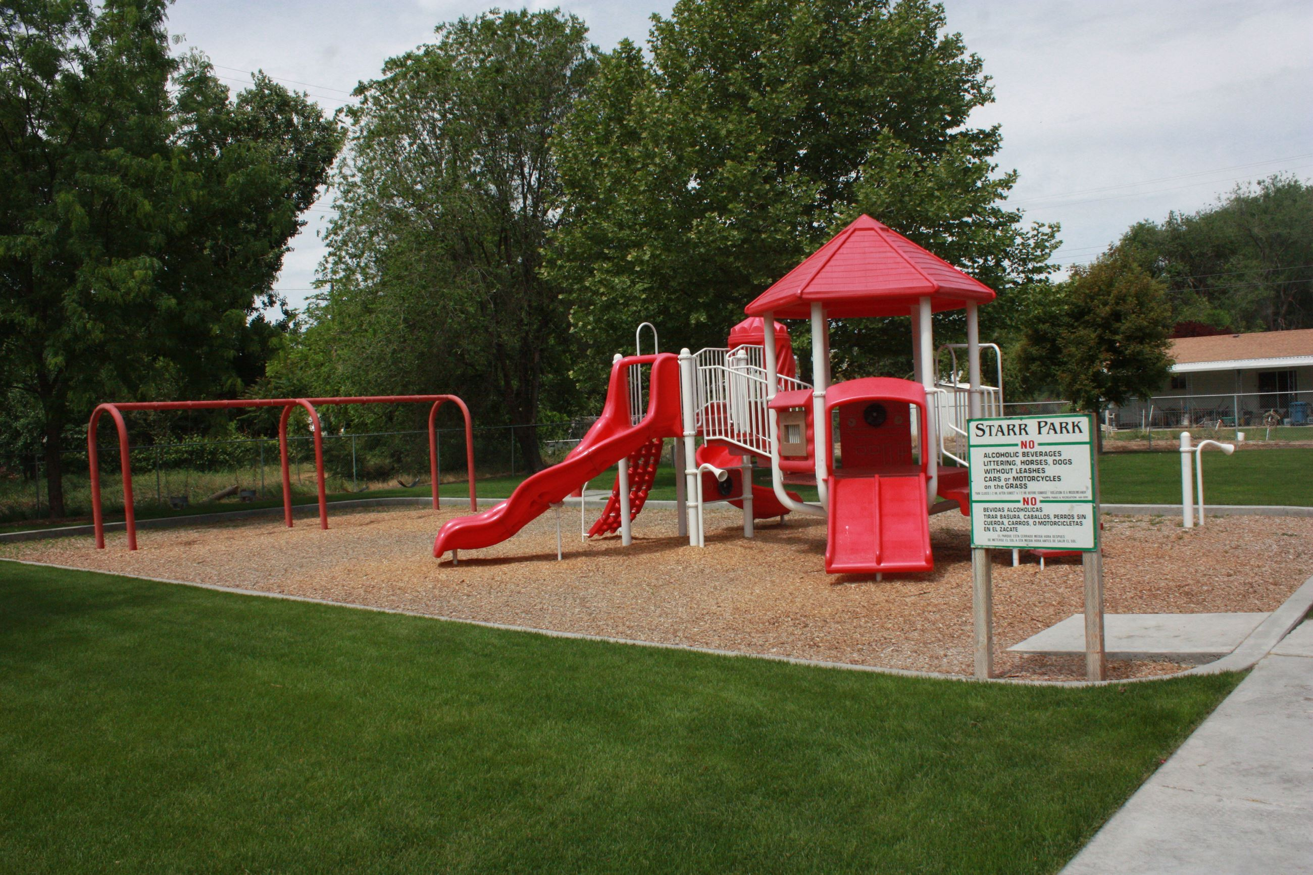 Red and white playground structure and four swings