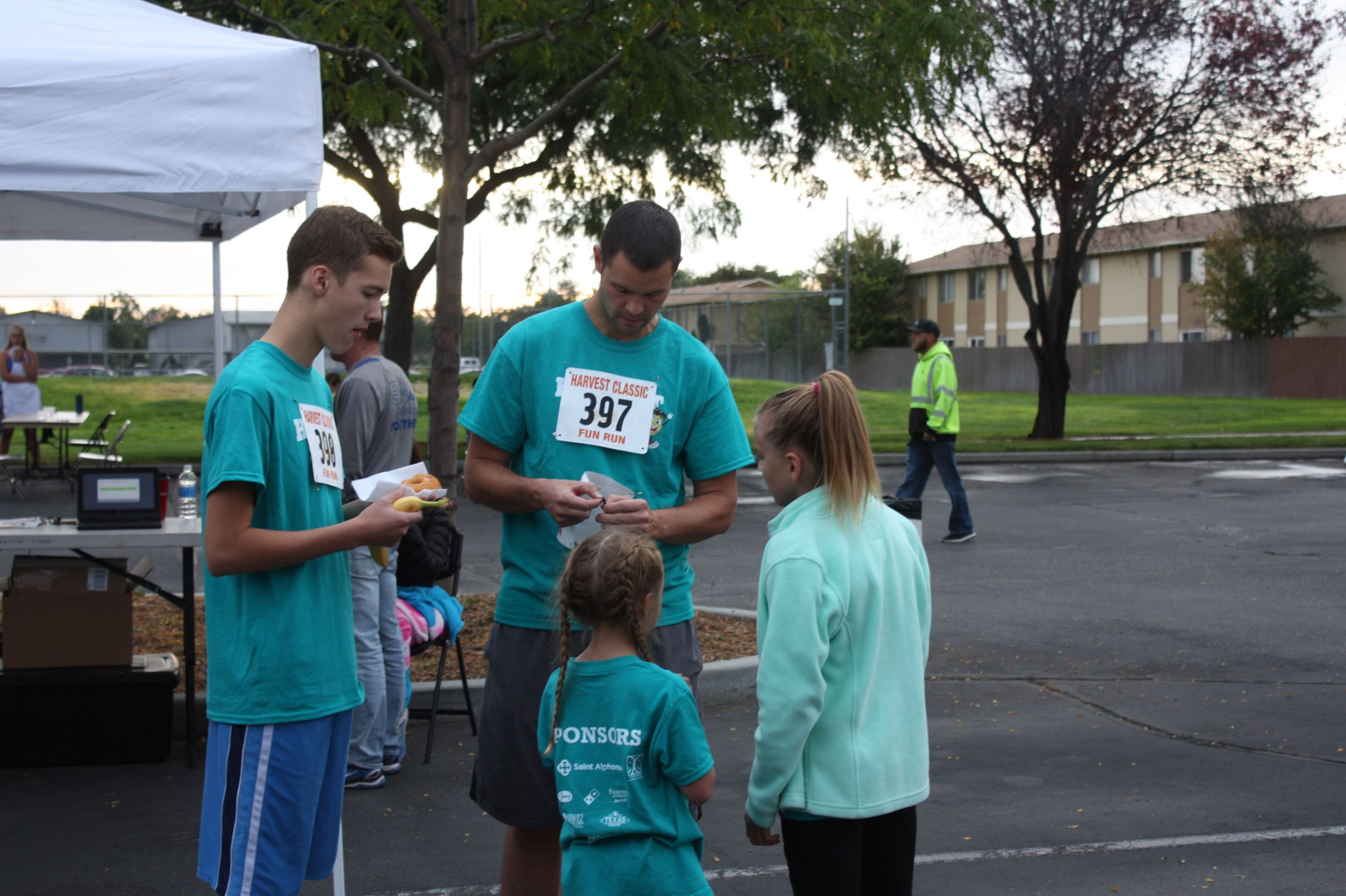 Man and children putting on race numbers at Harvest Classic