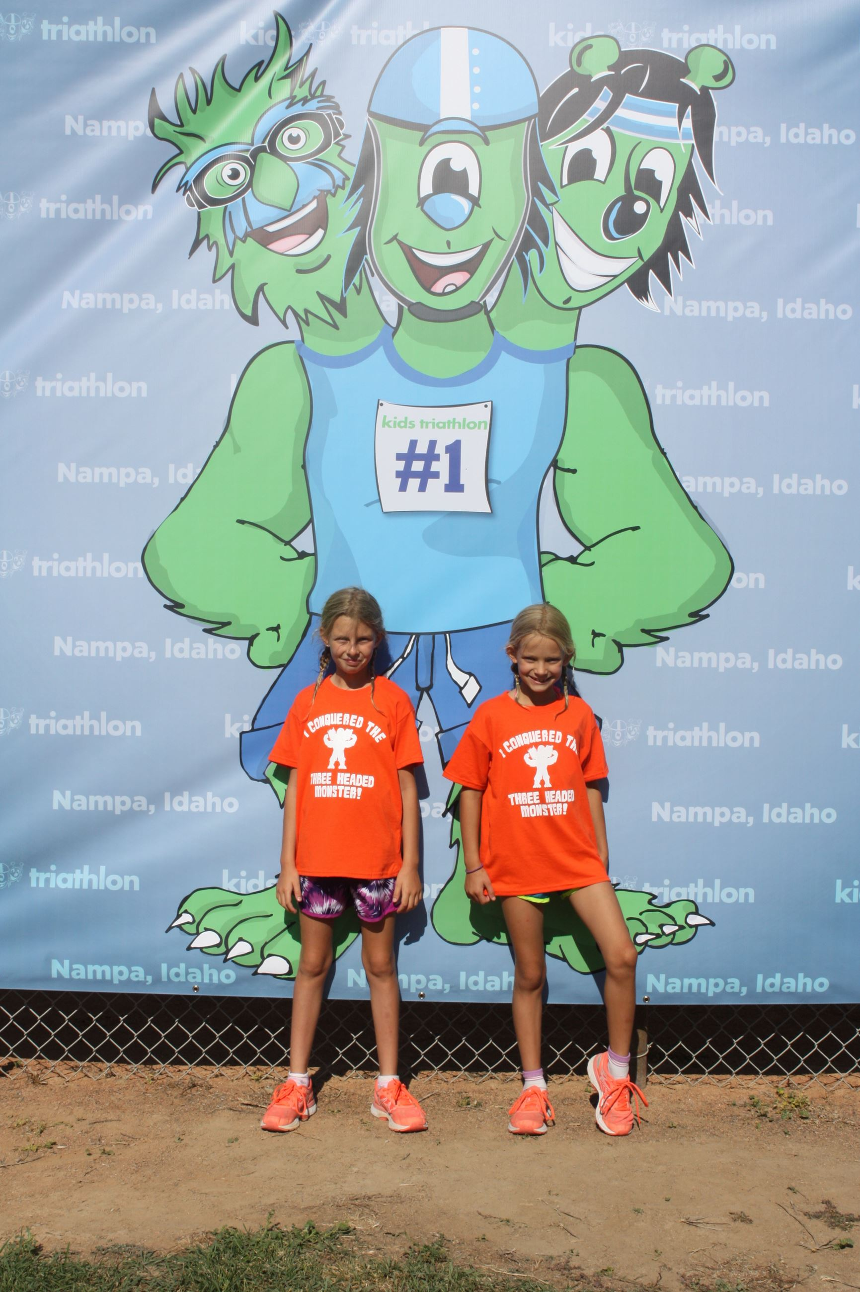 Two girls in front of monster banner at the Kids Triathlon