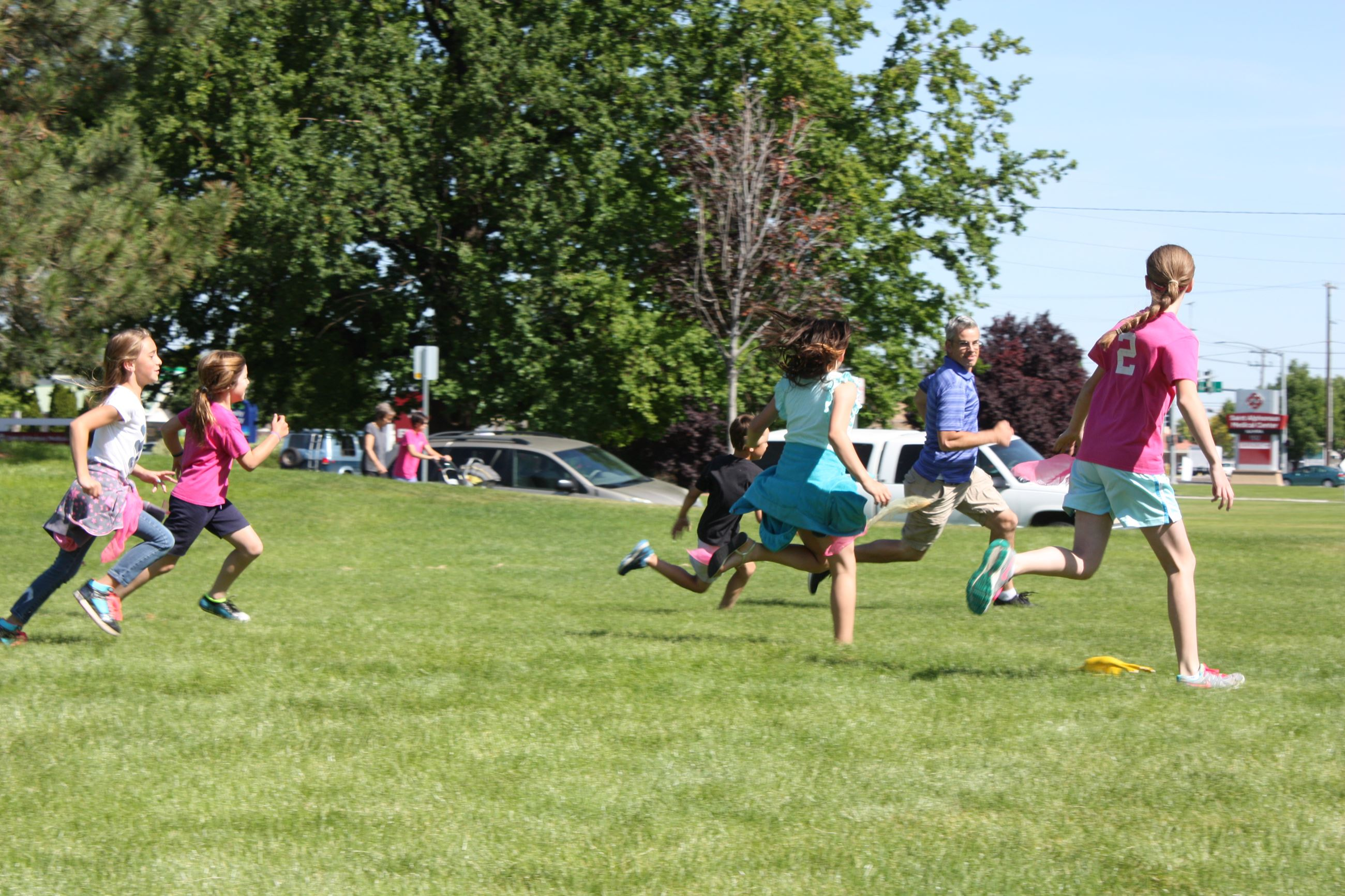 Children running on the grass at Traveling Playground