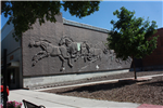 Stone wall with running horses engraved on it.